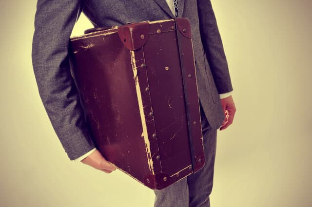 man in suit with an old suitcase